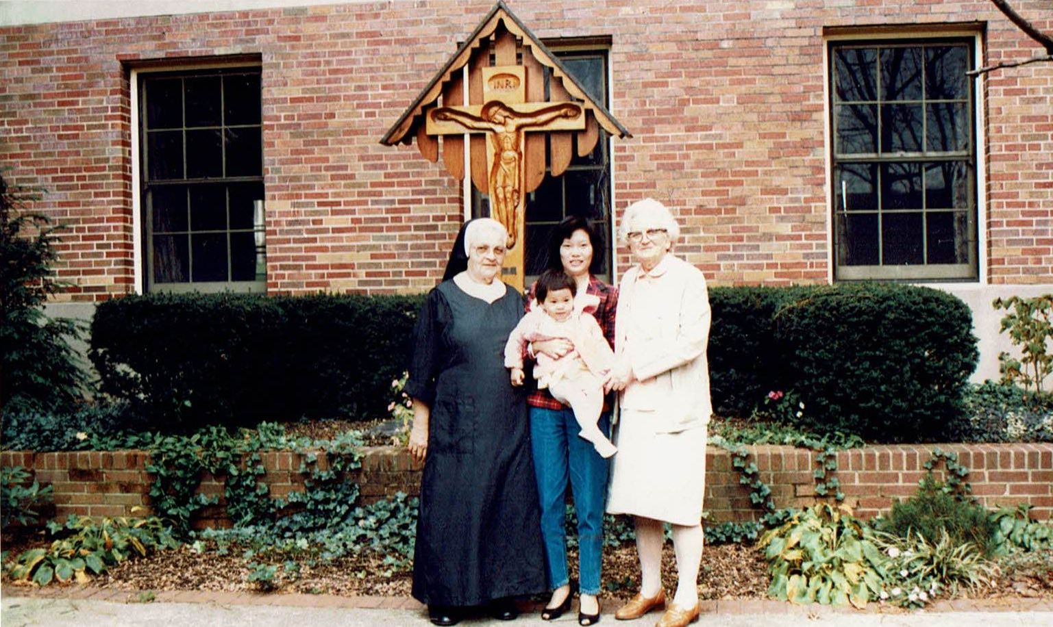 Theresa Vu and daughter Thanh with Benedictine Sisters Sr. Thomas (left in black habit) and Sr. Silvester, in the courtyard of St. Walburg Monastery in Villa Hills.
