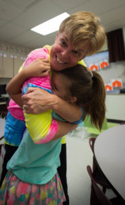 Kindergarten teacher Lori Maddux hugs student Elissa Brown duringParent Outreach night (Photo by Bobby Ellis)