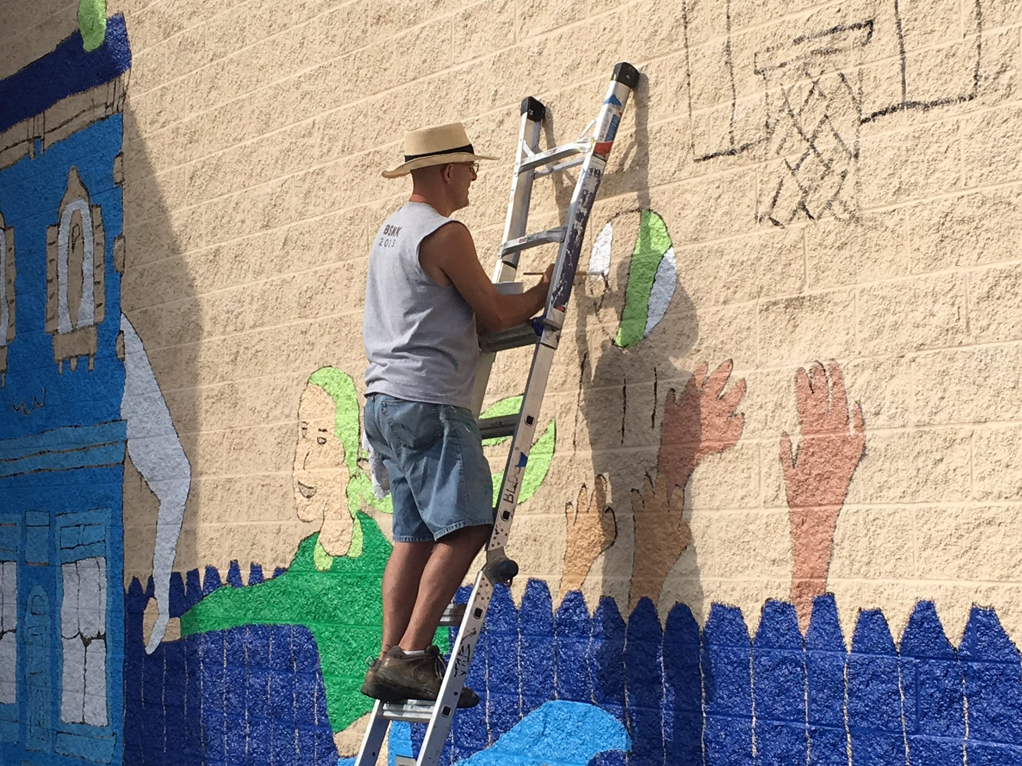 "Local artist Kevin T. Kelly works on the ""Love the Cov""mural Thursday (photos by Mark Hansel)"