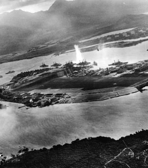 A rare photo taken by a Japanese pilot in the first minutes of the attack on Pearl Harbor. The first bombs may be seen falling on Battleship Row. (U.S. Navy photo.)