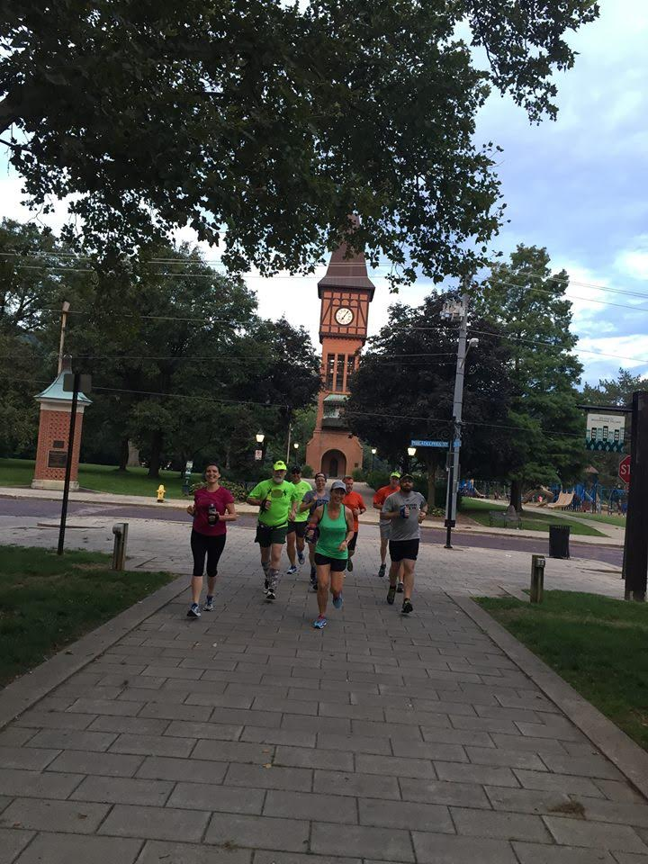 As this group of runners takes off along MainStrasse Village in Covington, with the Goebel Park clock tower in the background, the question arises: What are they thinking? (Photo provided)