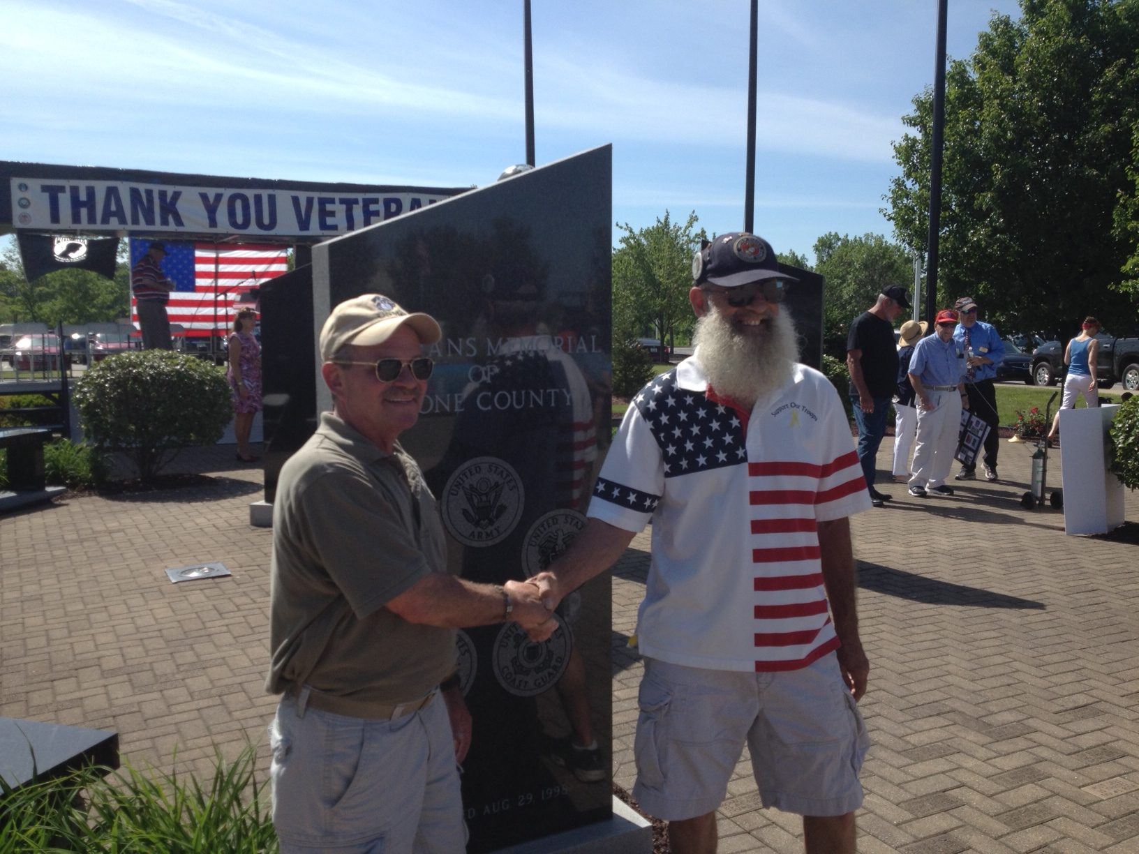 Jim Perkins of Burlington (left), shakes hands with Keith Maupin in front of the Florence Veteran's Memorial. Maupin's son Matt Maupin was killed after being captured in Iraq in 2004.